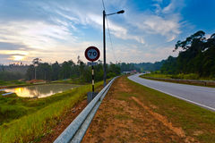 Rural road in Malaysia. A rural road in Malaysia showing the speed limit at sunrise Stock Images