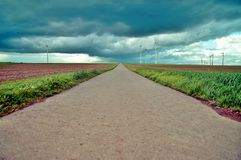 Rural road in the middle of green grain fields and Wind turbines in green landscape stock photography