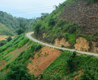 A rural road with mountain background Royalty Free Stock Photo