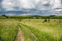 Rural road over fields Stock Images