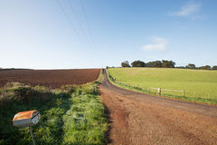 Rural road past ploughed field Royalty Free Stock Image