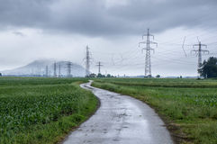 Rural road and power lines. Among fields Stock Photography