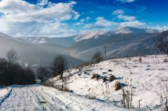 Rural road in snowy mountainous area. Beautiful winter scenery on a bright sunny day. mountains with snowy tops in a far distance Royalty Free Stock Photo