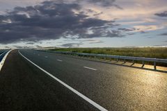 Rural road in the sunset. Asphalt road High way Empty curved road clouds and sky at sunset Royalty Free Stock Image