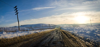 Rural road on a sunset with snow Royalty Free Stock Images
