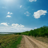 Rural road to horizon under cloudy sky Stock Image