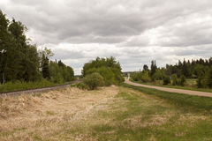 Rural road and train track running parallel Royalty Free Stock Photography