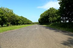 Rural road turns to right against the blue sky Stock Photo
