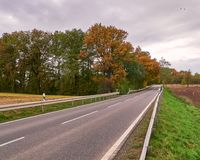 Rural road under cloudy sky Royalty Free Stock Image