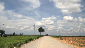 Rural road with wind turbines generating electricity stock video