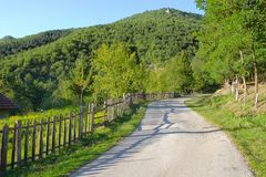 Rural Road With Wooden Fence In Serbia. Old fence along rural road of Kamena Gora, Serbia royalty free stock photo