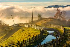 Rural road among the wooden fences in morning fog. Spectacular scenery in mountains at sunrise Royalty Free Stock Images