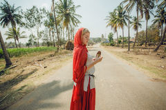 Rural road and young woman in red scarf standing with leaves of exotic trees in hands. Asia travel concept Royalty Free Stock Photo