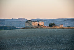 Rural ruin in sicily, southern italy. A rural ruin in the light of dawn in the middle of a arid field and with some mountains on the background Royalty Free Stock Photos
