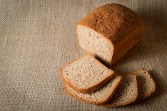 Rural rye bread sliced on linen tablecloth stock photography