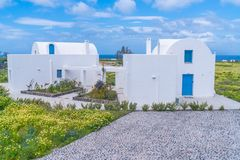 Rural Santorini landscape with traditional white house and wild flowers stock photos