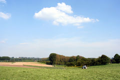 Rural scene. A field with tractor and cloudy sky at the background stock photo