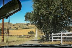Rural scene in California seen from inside a vehicle. Panoramic view captured from the inside of a vehicle circulating on a rural dirt road crossing between Royalty Free Stock Photography
