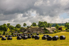 Rural scene in Cumbria. Scenic rural landscape with covered hay bales in the foreground, Cumbria, England Stock Image