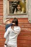 Rural scene with one year old baby boy with his mother outdoors looking at cottage window with grandmother inside Stock Images
