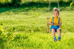 Rural scene with toddler boy swinging outdoors. Portrait of toddler child swinging outdoors. Rural scene with one year old baby boy at swing. Healthy preschool Stock Photography