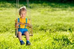 Rural scene with toddler boy swinging outdoors. Portrait of toddler child swinging outdoors. Rural scene with one year old baby boy at swing. Healthy preschool Royalty Free Stock Photo