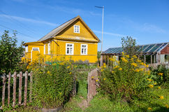 Rural scene with yellow flowers and house Royalty Free Stock Photos