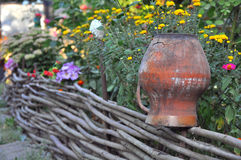 Rural scenery - old clay pots on a wattled fence near flowers Stock Photography