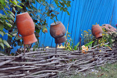 Rural scenery - old clay pots on a wattled fence near flowers Stock Image