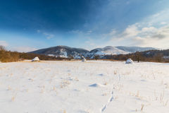 Rural scenery with snow covered fields and haystacks, in winter Stock Photo