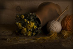 Rural Still Life. Yellow autumn flowers in brown pottery with orange and beige yarn balls and wooden pin against the wooden background, still life photography in Royalty Free Stock Photo