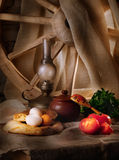 Rural still life. With oil lamp, bread and vegetables, wooden wheel on background, light painting Royalty Free Stock Photos