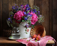 Rural still life with a bouquet of flowers and fruit. Peonies and irises in a milk can on wooden background. Basket with peaches Stock Photography
