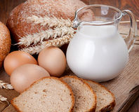 Rural still life. Bread, milk and eggs on the board Stock Photos