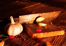 Rural still life spices, onion, garlic, pepper, knife Stock Images