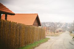 Rural street. Fence made of sharp wooden stakes. House with a red tiled roof. Cloudy autumn weather stock photography