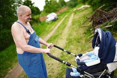 Rural style grandfather pushing a baby stroller Royalty Free Stock Photo
