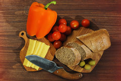 Rural styled cooking ingredients. Rural kitchen still life with brown bread, sliced cheese, bell pepper, tiny cherry tomatoes and pickled olives on the wooden stock images