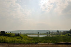 Rural summer landscape. The village and the lake in the morning hours. The fishermen on the lake stock photos