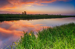 Rural summer sunset. Landscape with river and dramatic colorful sky Stock Photography