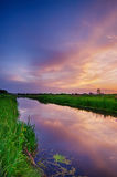 Rural summer sunset. Landscape with river and dramatic colorful sky Stock Images