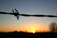 Rural Sunset. Barbed wire fence at sunset stock image