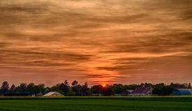 Rural sunset over a green meadow stock photography