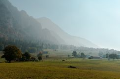 Rural Swiss countryside landscape with farm fields and misty mountains and forest in late autumn. Panorama rural Swiss countryside landscape with farm fields and stock photos