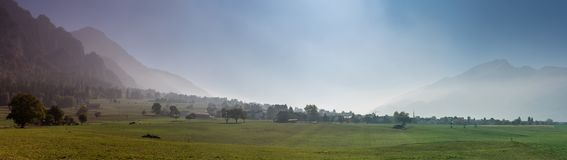 Rural Swiss countryside landscape with farm fields and misty mountains and forest in late autumn. Panorama rural Swiss countryside landscape with farm fields and royalty free stock image