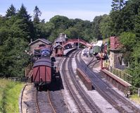 A rural train station UK. A rural train station in UK with three tracks, railway bridge, train engines and carriages. The setting is woodlands. The skies are stock photography