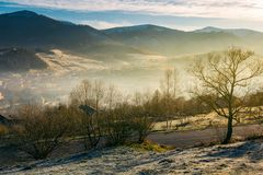 Rural valley in autumn at sunrise. Beautiful scenery in mountains. road down to village in haze and fog. distant mountain tops in snow royalty free stock image