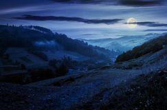 Rural valley with forested hills at night. In full moon light. beautiful summer landscape in Carpathian mountains Stock Photo