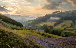 Rural valley with forested hills at sunrise. Beautiful summer landscape in Carpathian mountains Royalty Free Stock Image