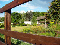 Rural water well and house behind old wooden fence Royalty Free Stock Image